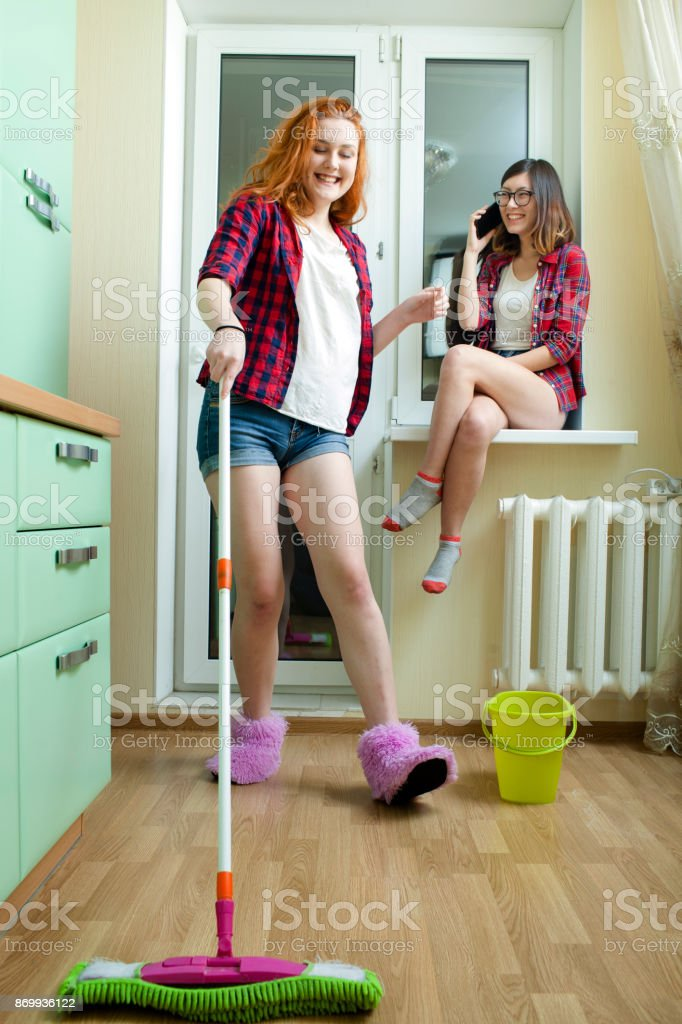 girl in the kitchen washes the floor stock photo