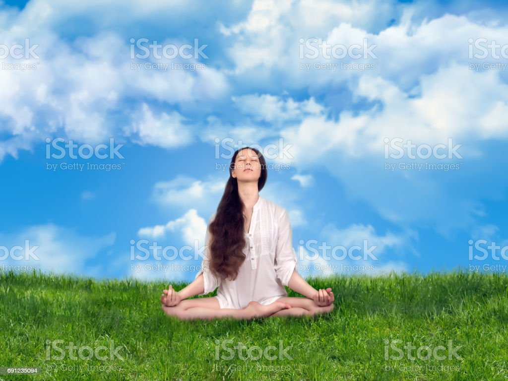 Girl in the Lotus position meditating. Green grass, blue sky, space stock photo