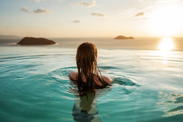 fille dans la piscine au coucher du soleil avec vue sur les montagnes et la mer - style de vie photos et images de collection