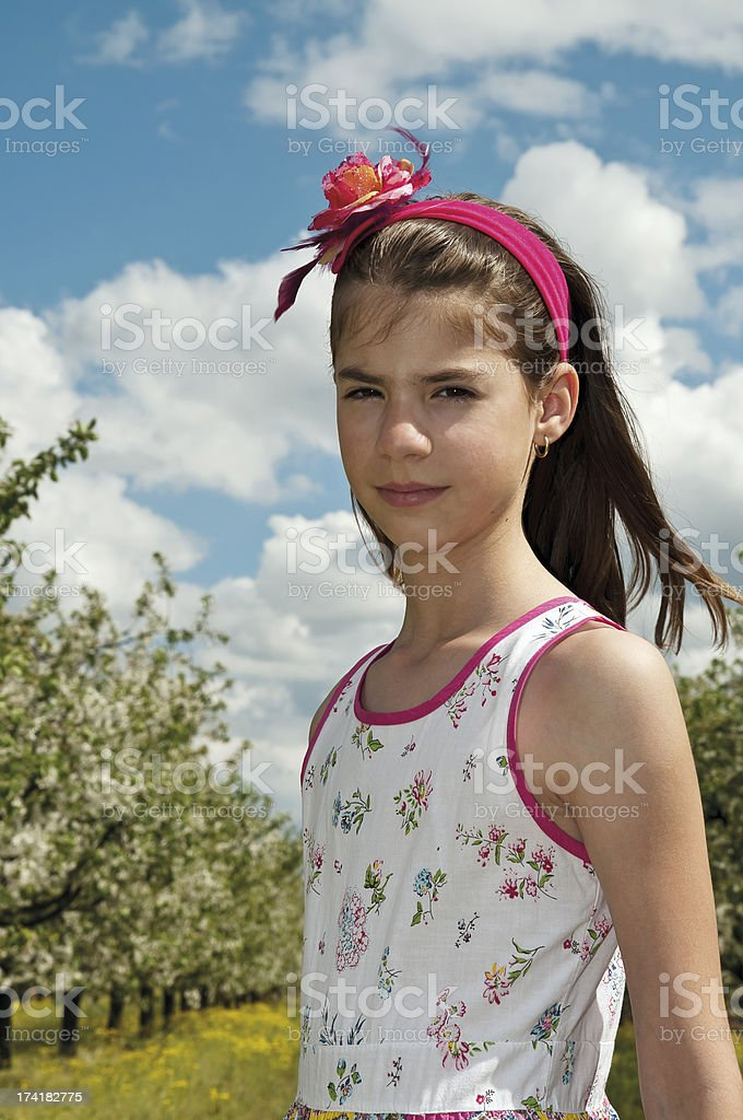 Girl in the sour cherry orchard looking sulky royalty-free stock photo