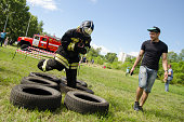 Komsomolsk-on-Amur, Russia - August 8, 2016. Public open Railroader's day. girl in the uniform of fireman jumps on obstacles course of tires
