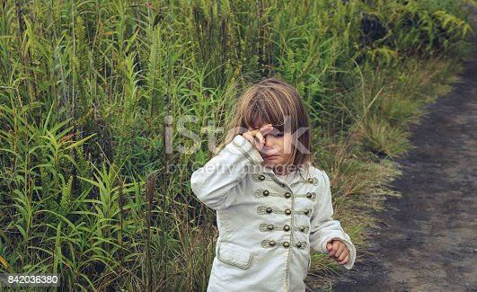 Sad little girl on a dirt road in a rural area