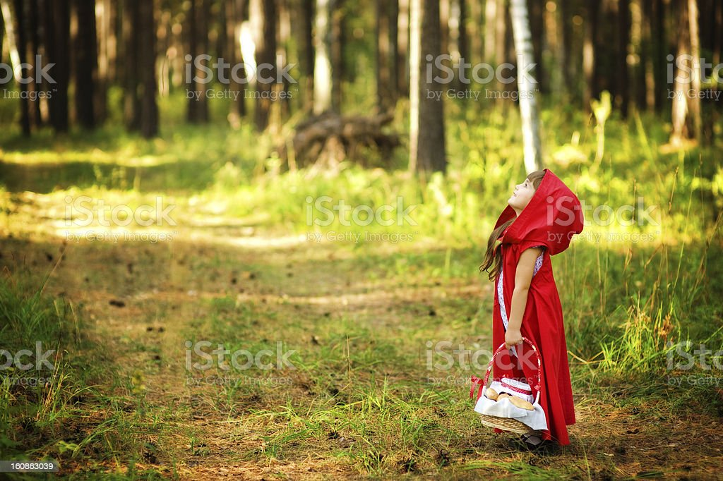 girl in the wood looks up royalty-free stock photo