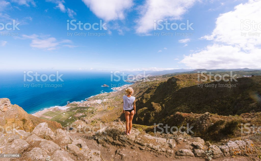 Girl in thongs standing on viewpoint above ocean and looking at mountains - fotografia de stock