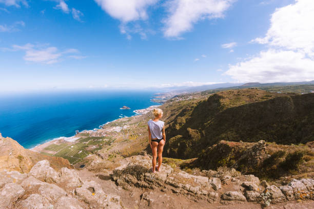 Girl in thongs standing on viewpoint above ocean and looking at mountains stock photo