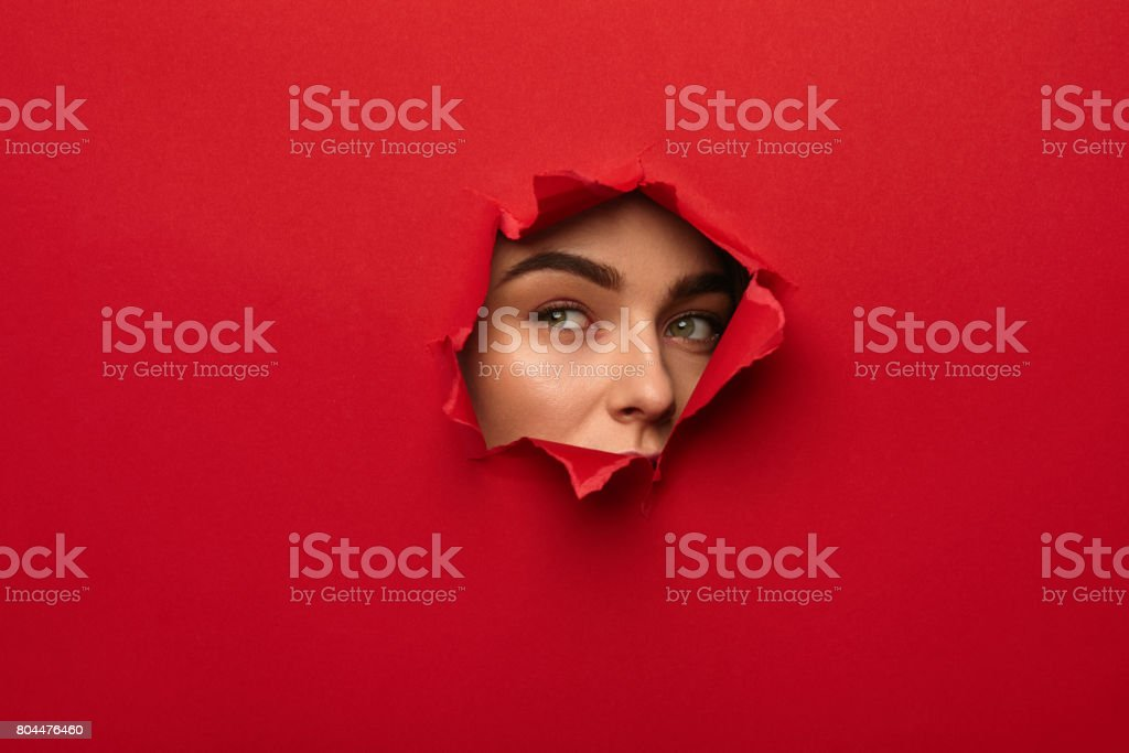 Girl in torn hole stock photo