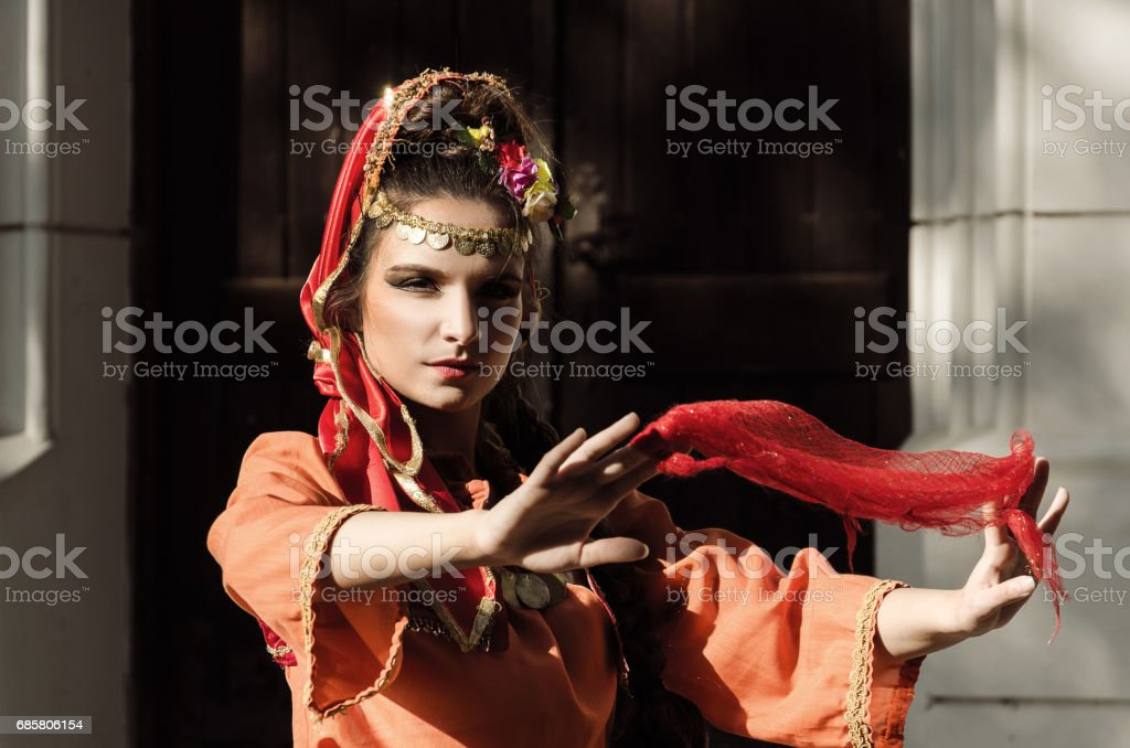 girl in Turkish costume dancing with a scarf in front of the large doors - foto de acervo