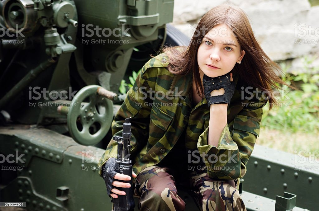 Girl in uniform with submachine sitting on gun carriage stock photo