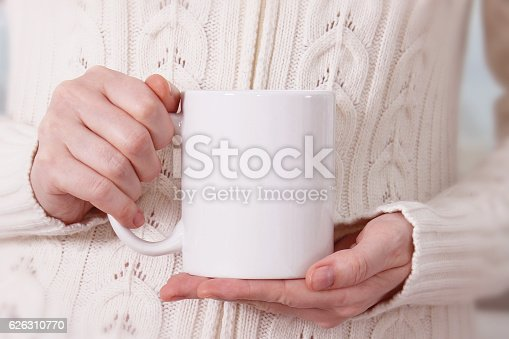 Girl in warm sweater is holding white mug in hands. Mockup for winter gifts design.
