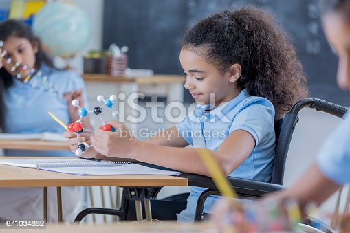 istock Girl in wheelchair concentrates in science class 671034882