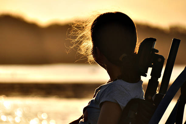 Girl In Wheelchair Teenage girl with cerebral palsy sits in a wheel chair watching the sunset by a river. paraplegic stock pictures, royalty-free photos & images