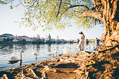 A girl in white dress and brown hat feeding white swans at Vltava river in Prague. View of the Vltava River and Charles Bridge.
