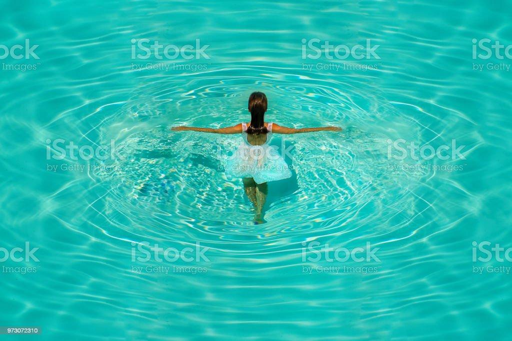91f0454bfd6792 Meisje in witte jurk in blauw water zwembad op een heldere zonnige middag.  royalty free