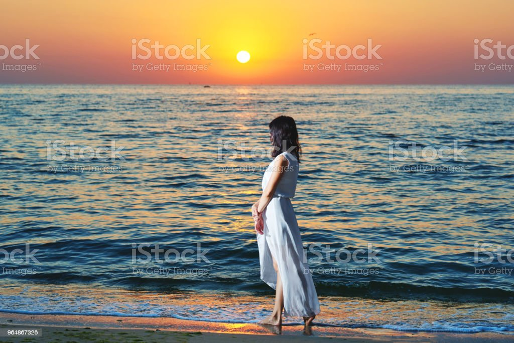 Girl in white dress on sunset's background. royalty-free stock photo