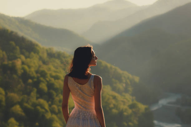 Girl in white dress standing back on the top of Caucasus mountain with a scenery view to sunset at green valley with river. Female travel nature concept stock photo