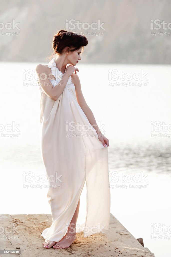 girl in white dress standing on a wodden pier royalty-free stock photo