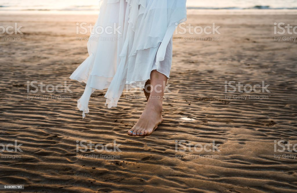 Girl in white dress walking on the beach stock photo