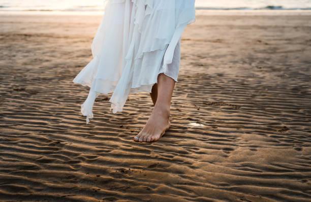 Girl in white dress walking on the beach stock photo