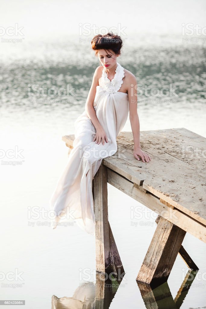 girl in white dresssitting on a wodden pier royalty-free stock photo