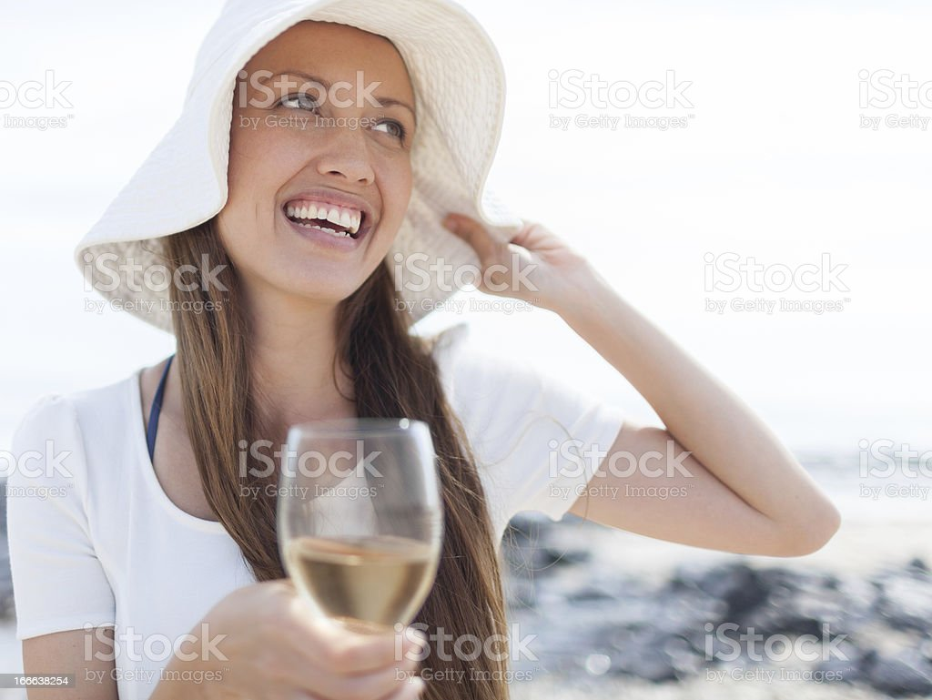 Girl in white hat on the beach stock photo