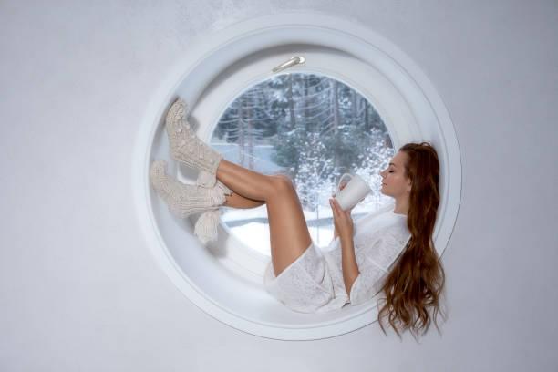 Chica en blanco deporte desgaste se encuentra en la ventana - foto de stock
