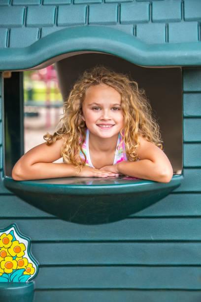 mädchen im fenster des outdoor-playhouse - mädchen spielhaus stock-fotos und bilder