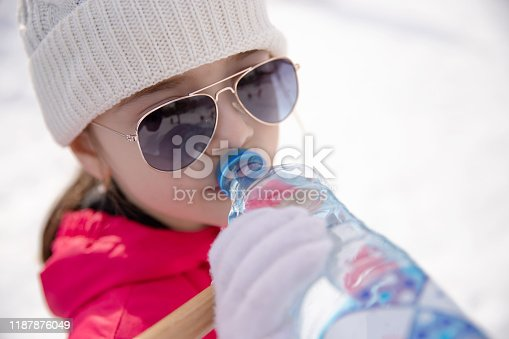 istock Girl in winter clothes drinking water 1187876049