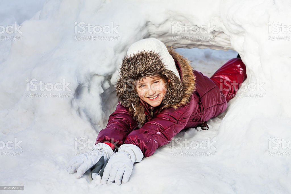 Girl in winter clothes playing at a snow hole stock photo