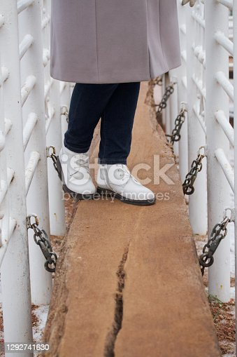 A girl in winter clothes walks in the park. Posing in the play area.