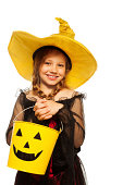 istock Girl in witch costume and spooky Halloween bucket 513254845