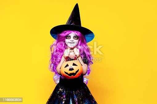 Small girl in Halloween witch dress and hat scaring and making faces isolated on yellow background. Trick or treat.