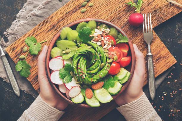 mädchen im wollpullover hält eine schale mit veganer salat mit sichtbaren hände. gesunde vegane ernährung-salat mit frischem gemüse. ansicht von oben - radieschen salat stock-fotos und bilder