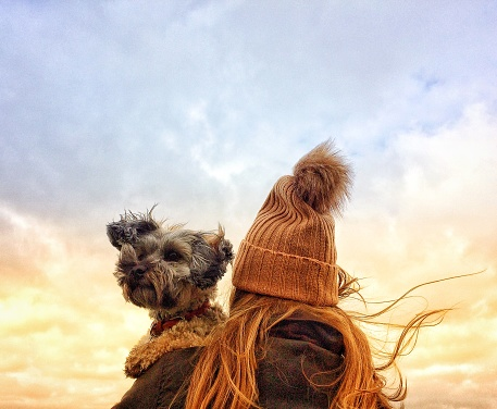 Girl in Wooly Hat holding her dog on a windy day
