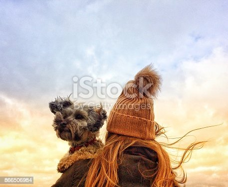 istock Girl in Wooly Hat holding her dog on a windy day 866506984