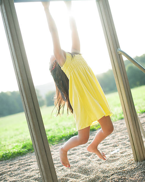 girl in yellow dress swing on bar at playground - horizontal bar stock photos and pictures