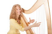 girl in yellow playing the harp against white background