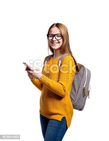 istock Girl in yellow sweater, holding smartphone, taking selfie, isola 623944000