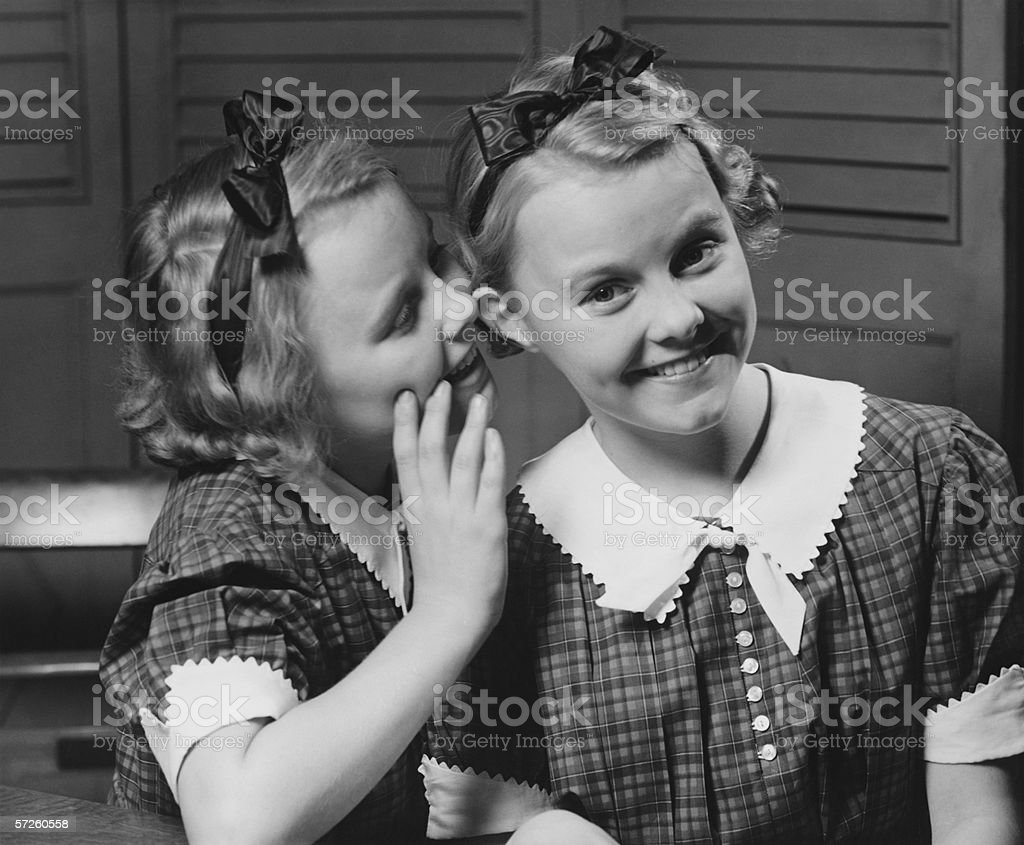 Girl (12-13) indoors whispering into ear of twin sister, (B&W) royalty-free stock photo