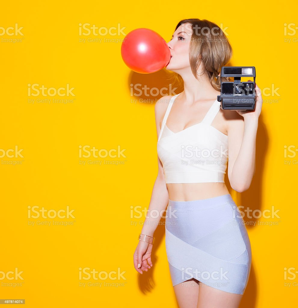 Girl inflates the bubble from chewing gum and a camera stock photo