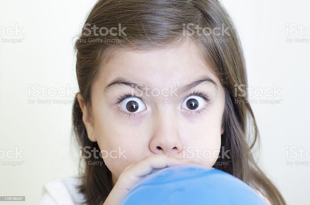 Girl inflatig a balloon stock photo