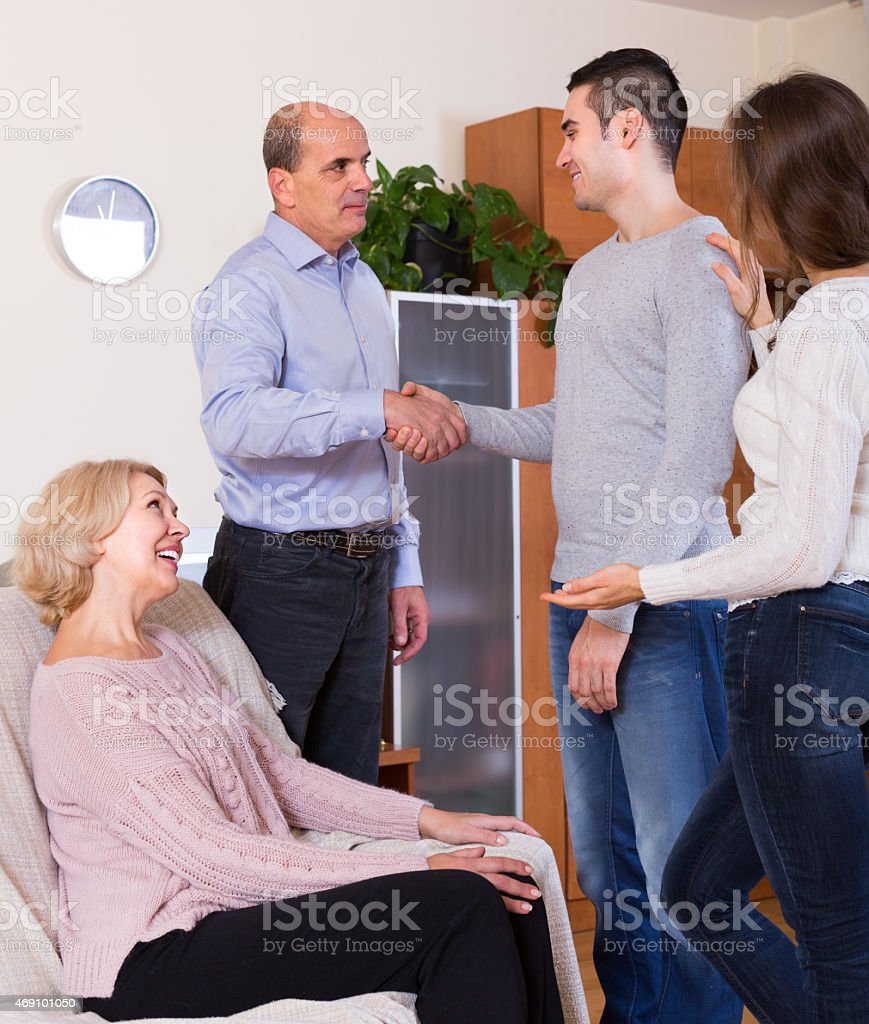 Girl introducing boyfriend to parents stock photo