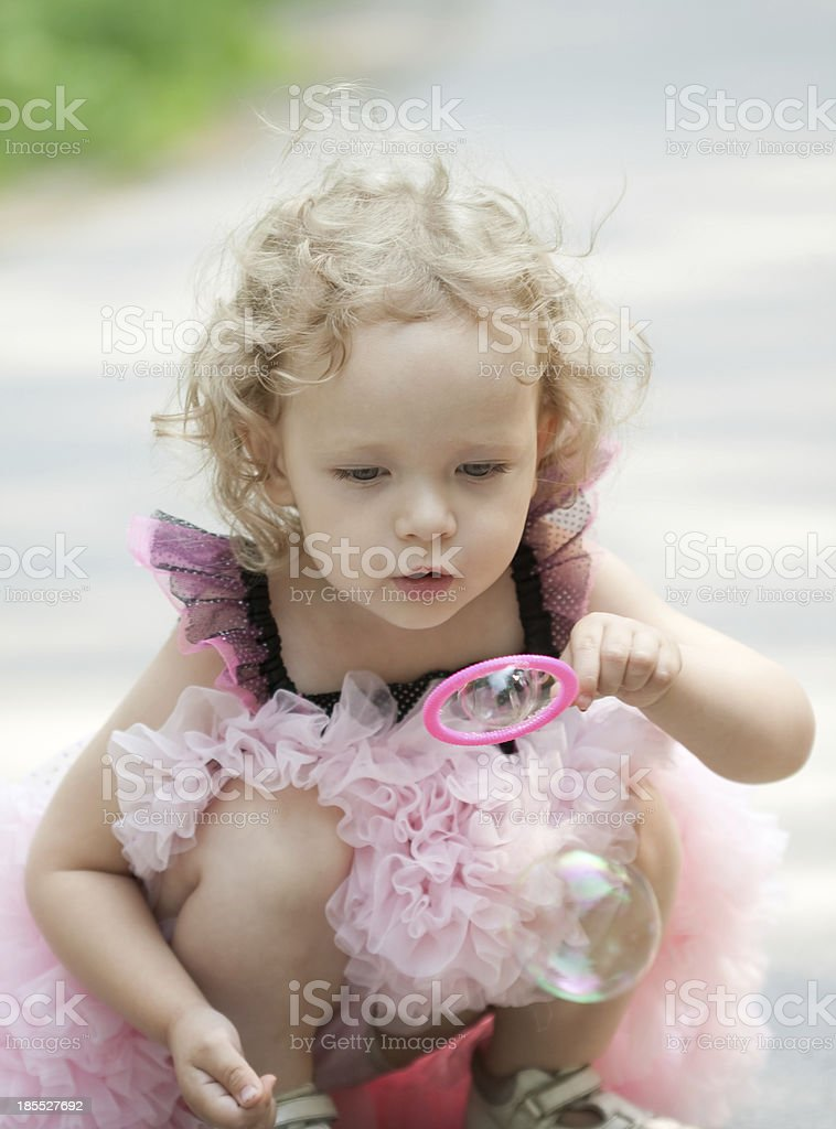 Girl is blowing soap bubbles royalty-free stock photo