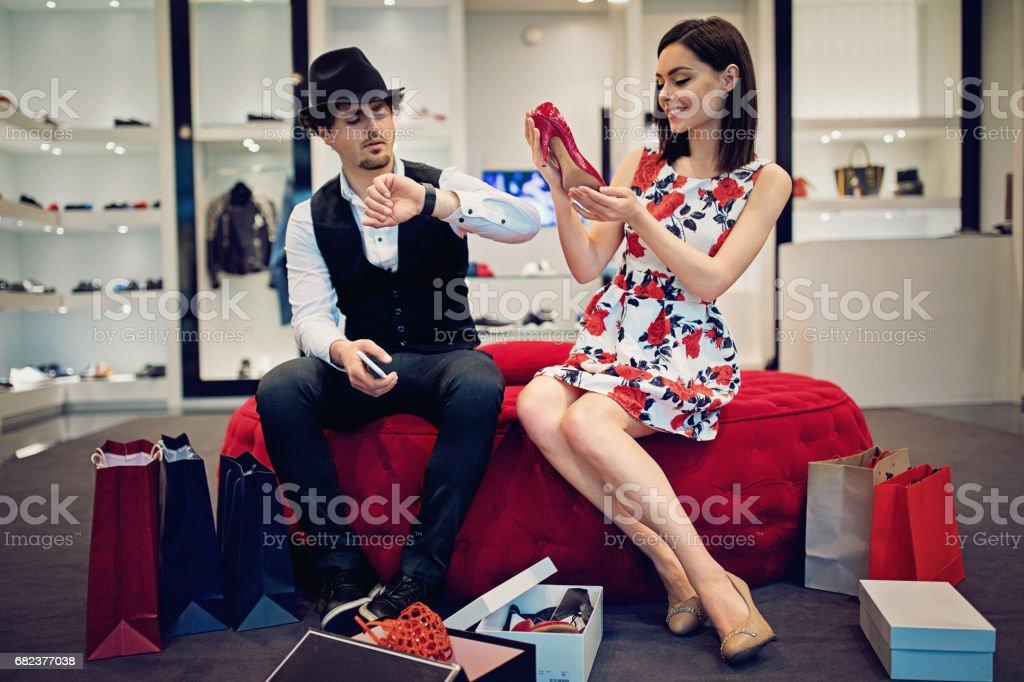 Girl is choosing a new shoes till her companion waiting bored in the shoes store foto de stock libre de derechos