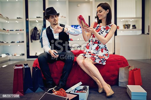 Girl is choosing a new shoes till her companion waiting bored in the shoes store