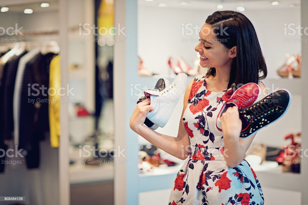 Girl is choosing shoes in a boutique and make fun stock photo