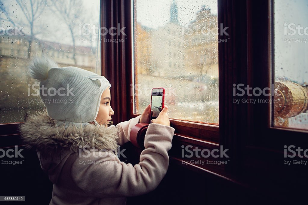 Girl is crossing river in the boat and taking photos stock photo
