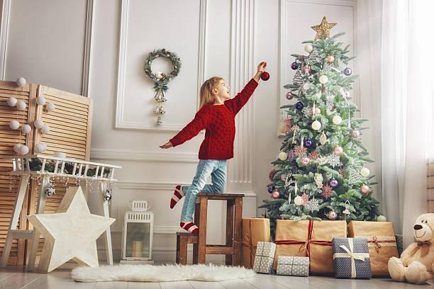 girl is decorating the christmas tree - weihnachten haus dekoration stock-fotos und bilder