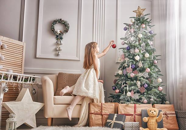 girl is decorating the christmas tree - weihnachtlich dekorieren stock-fotos und bilder