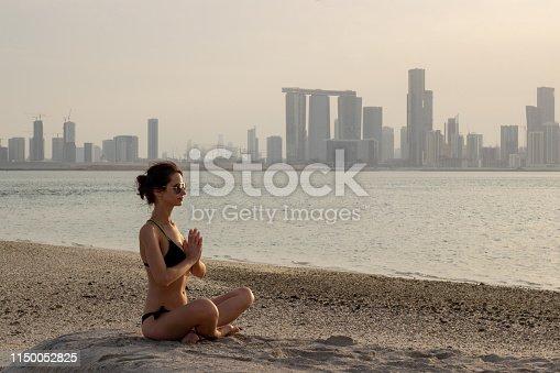 591835714 istock photo Girl is doing asana at the beach resort in Abu Dhabi 1150052825