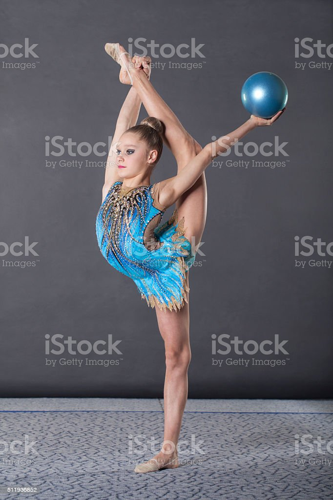 Girl is engaged in rhythmic gymnastics, sitting on the floor with a...